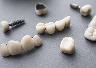 dental implants, crowns, and bridges lying on a flat surface