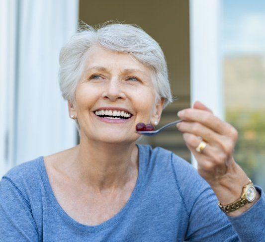 elderly lady eating fruit with a spoon