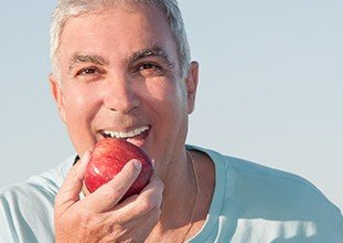elderly man biting into a red apple