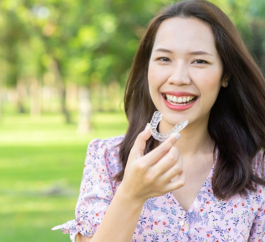 Smiling woman holding Invisalign in Raleigh