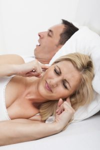 woman plugging ears from spouse snoring