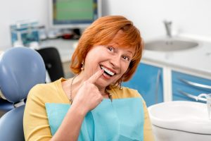 woman smiling pointing at dental implants