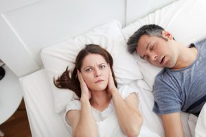A woman covering her ears in bed due to her snoring partner.