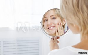Woman looking at smile in mirror.