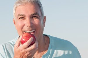 older man smiling holding apple