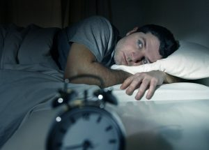 a man awake in bed in the early morning hours