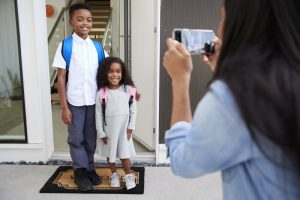parent taking back-to-school pictures of their children