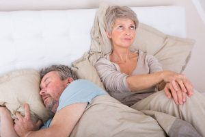 older woman angry at man snoring