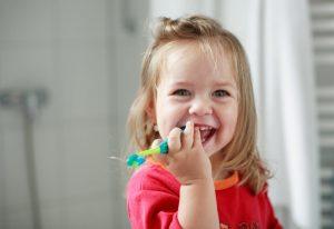 little girl holding her toothbrush