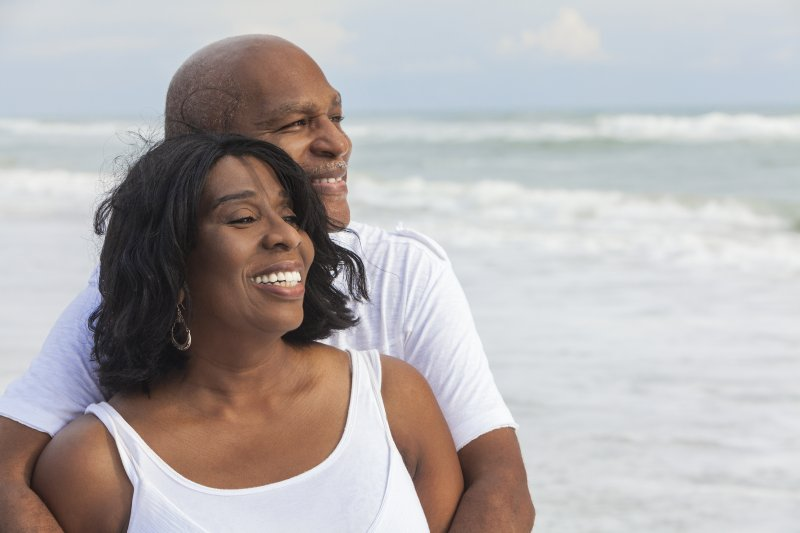 Older couple with dental implants in North Raleigh smiling outside