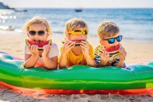 three children eating watermelon on the beach to prevent dental emergencies