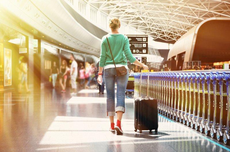 Woman traveling with sleep apnea, dragging suitcase through airport